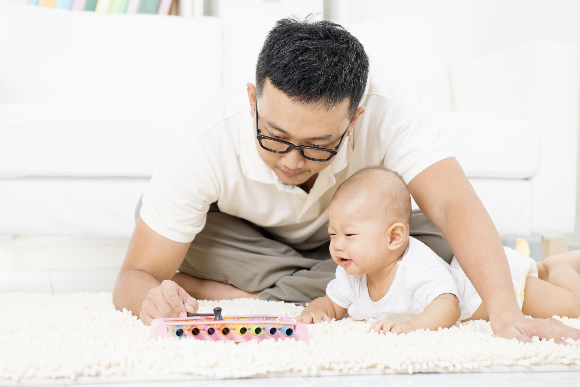 Father and baby playing music instrument. Sound development concept. Asian family lifestyle at home.