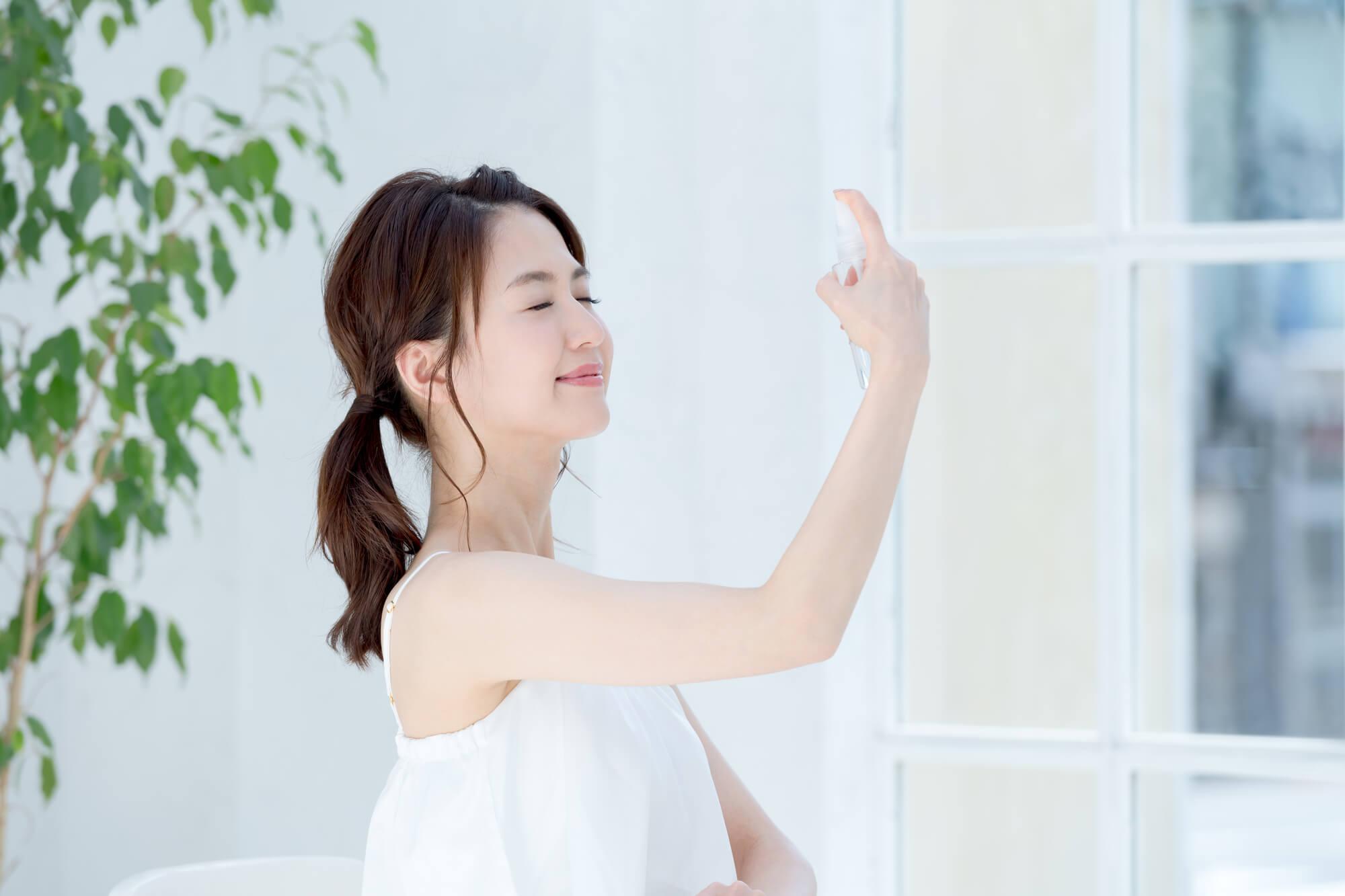 化粧水をふる女性