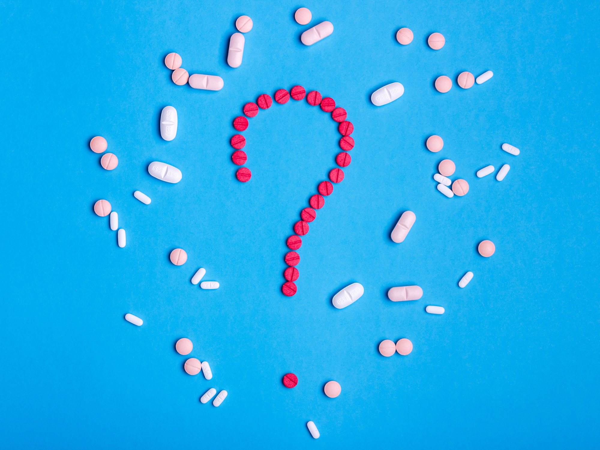 Question mark made from red medicine pills on a blue background