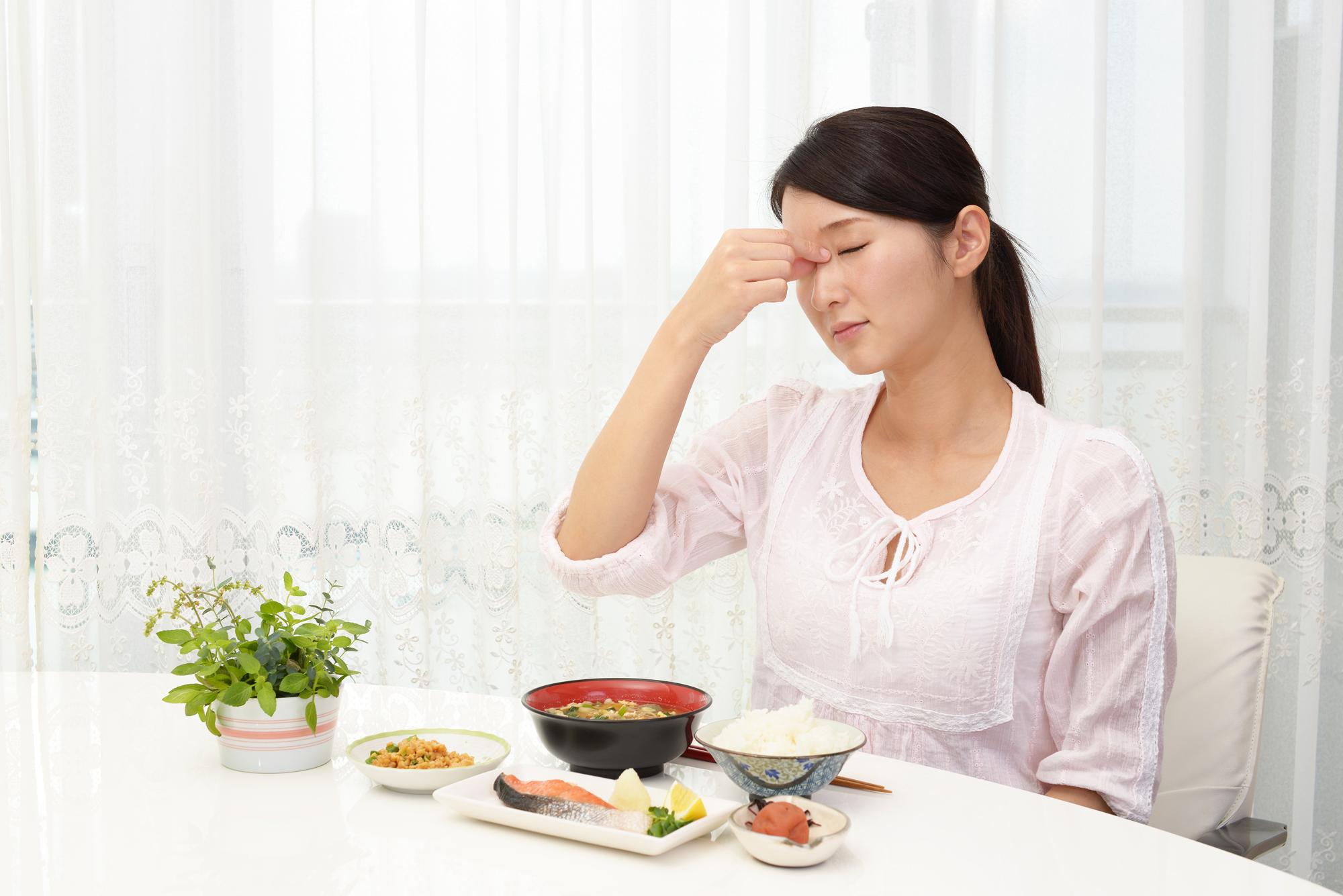 体調が悪い食事中の女性
