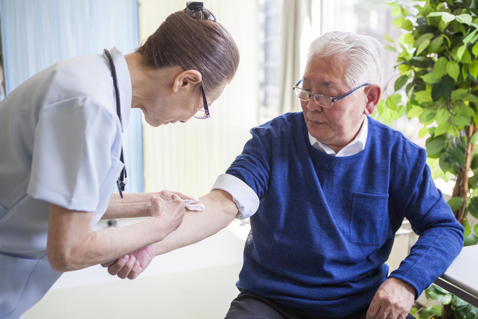 予防接種をする高齢者の男性